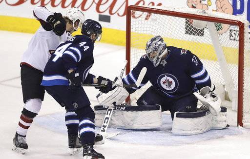The puck hits Winnipeg Jets' goaltender Connor Hellebuyck with Josh Morrissey (44) battling (37)Arizona Coyotes' Christian Dvorak (18) in front of the net late during third period NHL hockey action in Winnipeg, Manitoba Tuesday, Feb. 6, 2018. (Trevor Hagan/The Canadian Press via AP)