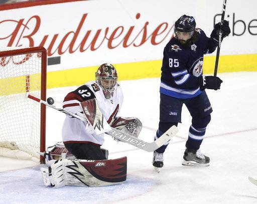 A Winnipeg Jets' shot hits the stick of Arizona Coyotes' goaltender Antti Raanta (32) with Mathieu Perreault (85) in front of the net during first period NHL hockey action in Winnipeg, Manitoba Tuesday, Feb. 6, 2018. (Trevor Hagan/The Canadian Press via AP)