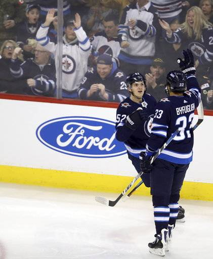 Winnipeg Jets' Jack Roslovic (52) and Dustin Byfuglien (33) celebrate after Roslovic scored against the Arizona Coyotes' during first period NHL hockey action in Winnipeg, Manitoba Tuesday, Feb. 6, 2018. (Trevor Hagan/The Canadian Press via AP)