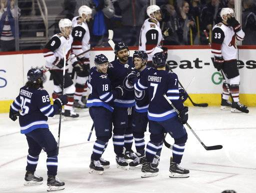 Winnipeg Jets' Mathieu Perreault (85), Bryan Little (18), Dustin Byfuglien (33), Nikolaj Ehlers (27) and Ben Chiarot (7) celebrate after Byfuglien scored against the Arizona Coyotes' during first period NHL hockey action in Winnipeg, Manitoba Tuesday, Feb. 6, 2018. (Trevor Hagan/The Canadian Press via AP)