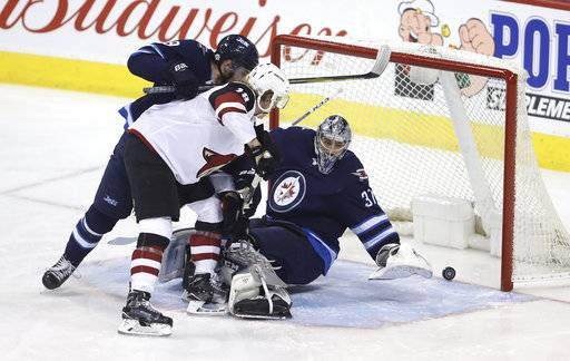 A shot by Kevin Connauton (44) rolls over the goal line behind Winnipeg Jets' goaltender Connor Hellebuyck (37) as Andrew Copp (9) battles with Christian Dvorak (18) in front the net during first period NHL hockey action in Winnipeg, Manitoba Tuesday, Feb. 6, 2018. (Trevor Hagan/The Canadian Press via AP)
