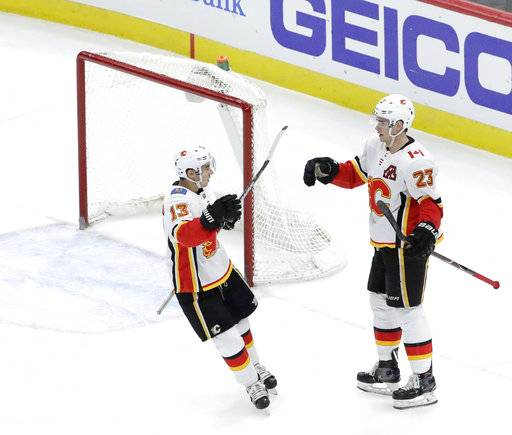 Calgary Flames' Sean Monahan (23) celebrates his goal with Johnny Gaudreau during the third period of an NHL hockey game against the Chicago Blackhawks on Tuesday, Feb. 6, 2018, in Chicago. The Flames won 3-2.