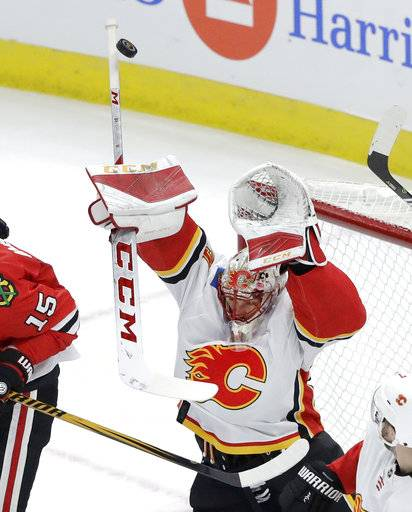 Calgary Flames goaltender Mike Smith goes after a high shot during the second period of the team's NHL hockey game against the Chicago Blackhawks on Tuesday, Feb. 6, 2018, in Chicago.
