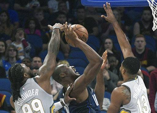 Cleveland Cavaliers forward Jae Crowder (99) blocks a shot by Orlando Magic center Bismack Biyombo (11) as Cavaliers center Tristan Thompson (13) helps during the first half of NBA basketball game Tuesday, Feb. 6, 2018, in Orlando, Fla.