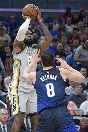 Cleveland Cavaliers forward LeBron James (23) goes up for a shot in front of Orlando Magic guard Mario Hezonja (8) during the first half of NBA basketball game Tuesday, Feb. 6, 2018, in Orlando, Fla.