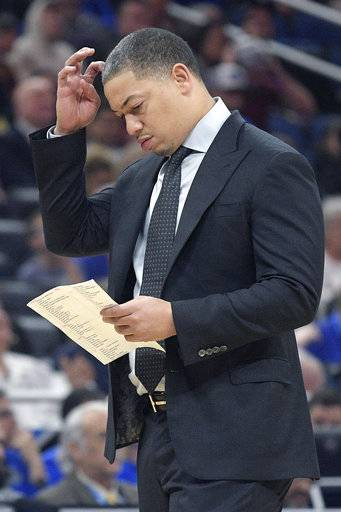 Cleveland Cavaliers head coach Tyronn Lue checks his notes during a timeout in the first half of NBA basketball game against the Orlando Magic Tuesday, Feb. 6, 2018, in Orlando, Fla.