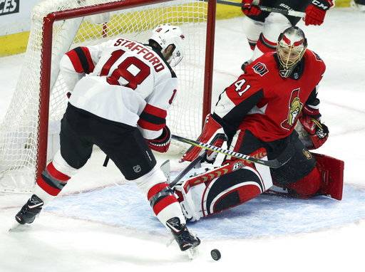 New Jersey Devils' Drew Stafford (18) tries to corral a rebound in front of Ottawa Senators goaltender Craig Anderson during the second period of an NHL hockey game Tuesday, Feb. 6, 2018, in Ottawa, Ontario. (Fred Chartrand/The Canadian Press via AP)