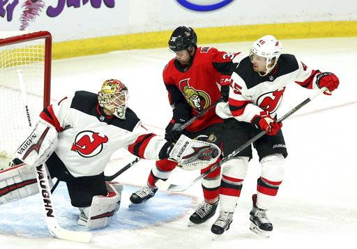 New Jersey Devils goaltender Keith Kinkaid (1) makes a glove save as Ottawa Senators Colin White (36) and Devils Sami Vatanen (45) look on during the first period of an NHL hockey game Tuesday, Feb. 6, 2018, in Ottawa, Ontario. (Fred Chartrand/The Canadian Press via AP)