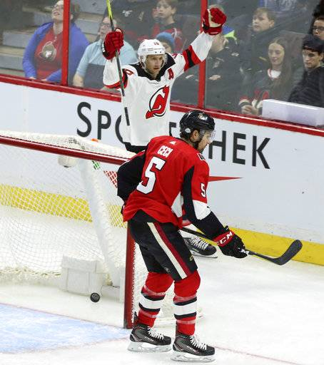 New Jersey Devils Travis Zajac (19) celebrates his goal as Ottawa Senators Cody Ceci (5) looks on during the first period of an NHL hockey game Tuesday, Feb. 6, 2018, in Ottawa, Ontario. (Fred Chartrand/The Canadian Press via AP)