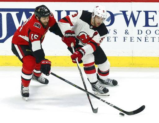 Ottawa Senator' Zack Smith (15) battles for the puck with New Jersey Devils Taylor Hall (9) during the second period of an NHL hockey game Tuesday, Feb. 6, 2018, in Ottawa, Ontario. (Fred Chartrand/The Canadian Press via AP)