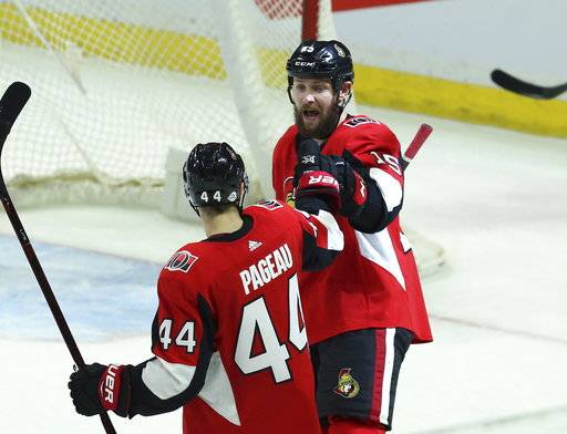 Ottawa Senators' Zack Smith (15) celebrates his goal against the New Jersey Devils with teammate Jean-Gabriel Pageau (44) during the second period of an NHL hockey game Tuesday, Feb. 6, 2018, in Ottawa, Ontario. (Fred Chartrand/The Canadian Press via AP)
