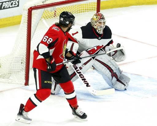 Ottawa Senators Mike Hoffman (68) tries to deflect the puck as New Jersey Devils goaltender Keith Kinkaid (1) reacts during the first period of an NHL hockey game Tuesday, Feb. 6, 2018, in Ottawa, Ontario. (Fred Chartrand/The Canadian Press via AP)