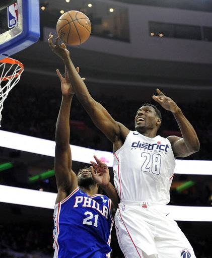 Washington Wizards' Ian Mahinmi (28) drives the ball to the basket over Philadelphia 76ers' Joel Embiid (21) in the first half of an NBA basketball game, Tuesday, Feb 6, 2018, in Philadelphia.