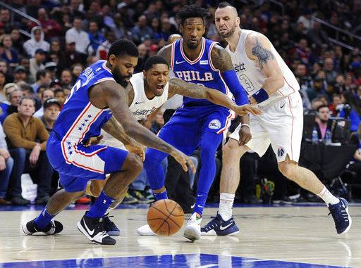 Washington Wizards' Bradley Beal (3) and Philadelphia 76ers' Amir Johnson (5) chase down a loose ball in the first half of an NBA basketball game, Tuesday, Feb 6, 2018, in Philadelphia.