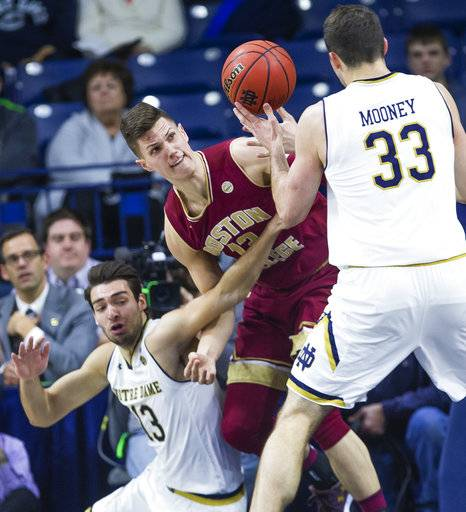 Notre Dame's Nikola Djogo (13) and John Mooney (33) fight for a loose ball with Boston College's Luka Krlajevic during an NCAA college basketball game in South Bend, Ind., Tuesday, Feb. 6, 2018. (Michael Caterina/South Bend Tribune via AP)