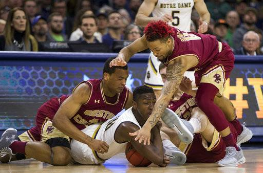 Notre Dame's T.J. Gibbs, center, competes for a loose ball with Boston College's Steffon Mitchell, left, Nik Popovic and Ervins Meznieks, right, during the first half of an NCAA college basketball game Tuesday, Feb. 6, 2018, in South Bend, Ind.