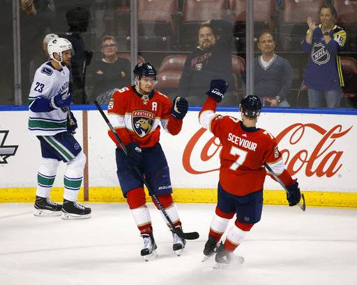 Florida Panthers center Aleksander Barkov, center, is congratulated by center Colton Sceviour (7) after Barkov scored during the third period of an NHL hockey game against the Vancouver Canucks, Tuesday, Feb. 6, 2018, in Sunrise, Fla. The Panthers defeated the Canucks 3-1.