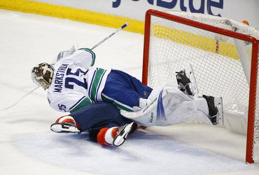 Vancouver Canucks goaltender Jacob Markstrom (25) flattens Florida Panthers left wing Jonathan Huberdeau during the second period of an NHL hockey game Tuesday, Feb. 6, 2018, in Sunrise, Fla.