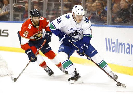 Vancouver Canucks center Bo Horvat (53) and Florida Panthers defenseman Aaron Ekblad (5) compete for the puck during the first period of an NHL hockey game Tuesday, Feb. 6, 2018, in Sunrise, Fla.