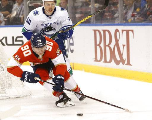 Florida Panthers center Jared McCann (90) reaches for the puck in front of Vancouver Canucks center Brendan Gaunce (50)  during the first period of an NHL hockey game, Tuesday, Feb. 6, 2018, in Sunrise, Fla.