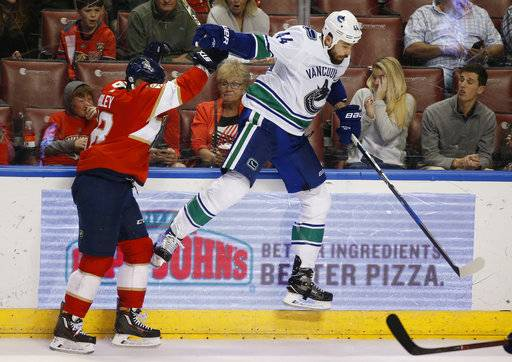 Florida Panthers center Micheal Haley, left, slams Vancouver Canucks defenseman Erik Gudbranson (44) into the boards during the second period of an NHL hockey game Tuesday, Feb. 6, 2018, in Sunrise, Fla. The Panthers defeated the Canucks 3-1.