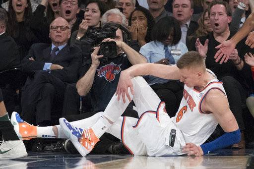 New York Knicks forward Kristaps Porzingis clutches his knee after a fall during the first half of the team's NBA basketball game against the Milwaukee Bucks, Tuesday, Feb. 6, 2018, at Madison Square Garden in New York.
