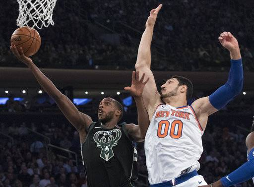 Milwaukee Bucks forward Khris Middleton (22) goes to the basket past New York Knicks center Enes Kanter (00) during the first half of an NBA basketball game, Tuesday, Feb. 6, 2018, at Madison Square Garden in New York.