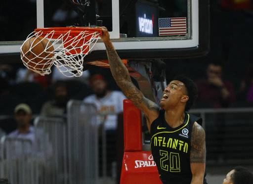 Atlanta Hawks forward John Collins (20) scores during the second half of the team's NBA basketball game against the Memphis Grizzlies on Tuesday, Feb. 6, 2018, in Atlanta. The Hawks won 108-82.