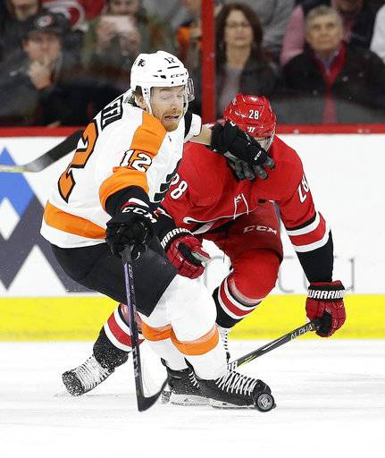 Philadelphia Flyers' Michael Raffl (12), of Austria, chases the puck with Carolina Hurricanes' Elias Lindholm (28), of Sweden, during the first period of an NHL hockey game in Raleigh, N.C., Tuesday, Feb. 6, 2018.