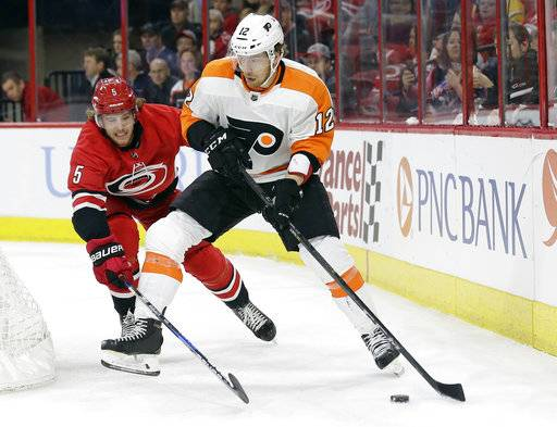 Carolina Hurricanes' Noah Hanifin (5) chases Philadelphia Flyers' Michael Raffl (12), of Austria during the first period of an NHL hockey game in Raleigh, N.C., Tuesday, Feb. 6, 2018.