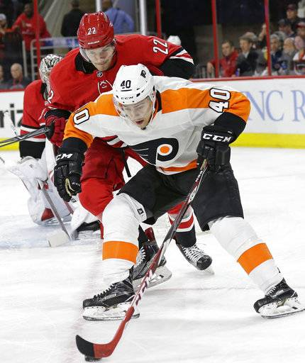 Carolina Hurricanes' Brett Pesce (22) chases Philadelphia Flyers' Jordan Weal (40) during the first period of an NHL hockey game in Raleigh, N.C., Tuesday, Feb. 6, 2018.