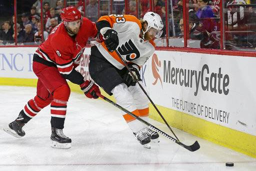 Carolina Hurricanes' Klas Dahlbeck (6), of Sweden, chases the puck with Philadelphia Flyers' Jakub Voracek (93), of the Czech Republic, during the first period of an NHL hockey game in Raleigh, N.C., Tuesday, Feb. 6, 2018.