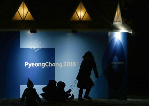 Children are pulled on a bobsleigh, in front of the 2018 Winter Olympics sign, in Pyeongchang, South Korea, Tuesday, Feb. 6, 2018.