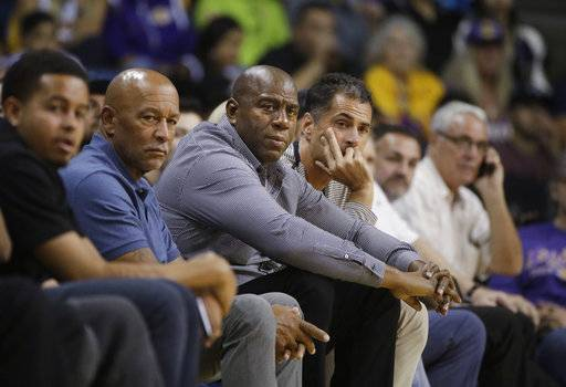 FILE - In this Oct. 4, 2017 file photo Los Angeles Lakers general manager Rob Pelinka, center right, and Magic Johnson watch the team's NBA preseason basketball game against the Denver Nuggets in Ontario, Calif. The Lakers have been fined $50,000 for violating the NBA's tampering rule again. League officials made the announcement Tuesday, Feb. 6, 2018 in response to an interview Johnson did with ESPN.