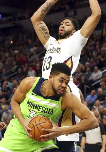 Minnesota Timberwolves' Karl-Anthony Towns, bottom, drives around New Orleans Pelicans' Anthony Davis, top, in the first half of an NBA basketball game Saturday, Feb. 3, 2018, in Minneapolis.