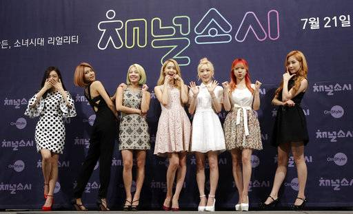 "FILE - In this July 21, 2015 file photo, South Korean girl group Girls' Generation pose for the media during a presentation to promote their new reality TV program ""Channel Girls' Generation"" in Seoul, South Korea. The clothes, the hair, the confidence , the look of Korean pop-music, or K-pop, can either feel like high fashion or just plain quirky. But that's what draws in fans to South Korea's most famous export. It will be hard to bypass this cultural phenomenon during the upcoming 2018 Olympic Winter Games."
