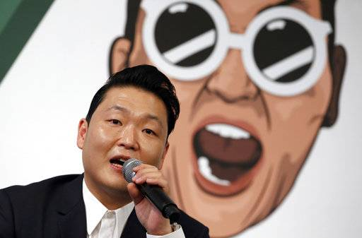 FILE - In this Nov. 30, 2015 file photo, South Korean singer PSY answers a reporter's question during a news conference on the release of his seventh album in Seoul, South Korea.  The clothes, the hair, the confidence , the look of Korean pop-music, or K-pop, can either feel like high fashion or just plain quirky. But that's what draws in fans to South Korea's most famous export. It will be hard to bypass this cultural phenomenon during the upcoming 2018 Olympic Winter Games.