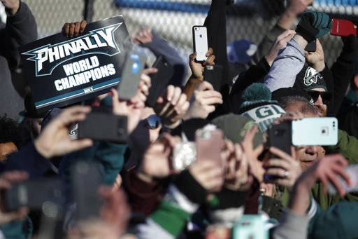 Philadelphia Eagles fan hold up smartphones as the team's airplane arrives at Philadelphia International Airport a day after defeating the New England Patriots in Super Bowl 52 in Minneapolis, Monday, Feb. 5, 2018.