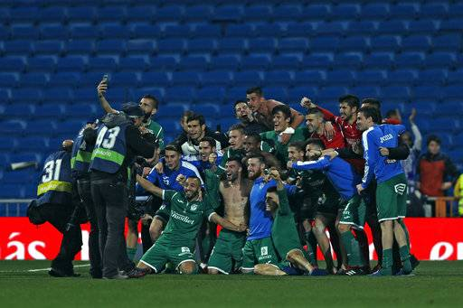 FILE - In this Jan. 24, 2018 file photo, Leganes' players celebrate their victory against Real Madrid at the end of the Spanish Copa del Rey quarterfinal second leg soccer match at the Santiago Bernabeu stadium in Madrid, Spain. The team everyone is talking about now is Leganes, the modest club based just south of the capital. It spent a decade in the third tier, from 2004-2014, before making the run that took the club to the first division in 2016.