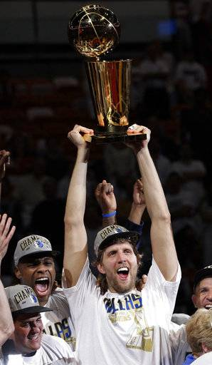 FILE - In this June 12, 2011, file photo, Dallas Mavericks' Dirk Nowitzki holds up the championship trophy after Game 6 of the NBA Finals basketball game against the Miami Heat in Miami. The Mavericks won 105-95 to win the series. Now in his 20th season, Nowitzki is comfortable with the idea that he led the Mavericks to their first championship and can try to help a younger core build toward making Dallas a title contender again.