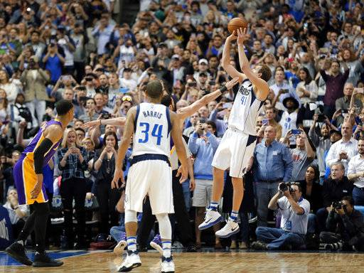 FILE - In this March 7, 2017, file photo, Dallas Mavericks' Devin Harris (34) watches as teammate Dirk Nowitzki (41), of Germany, makes a shot, giving Nowitzki his 30,000th career point, during the first half of an NBA basketball game against the Los Angeles Lakers in Dallas. Now in his 20th season, Nowitzki is comfortable with the idea that he led the Mavericks to their first championship and can try to help a younger core build toward making Dallas a title contender again.