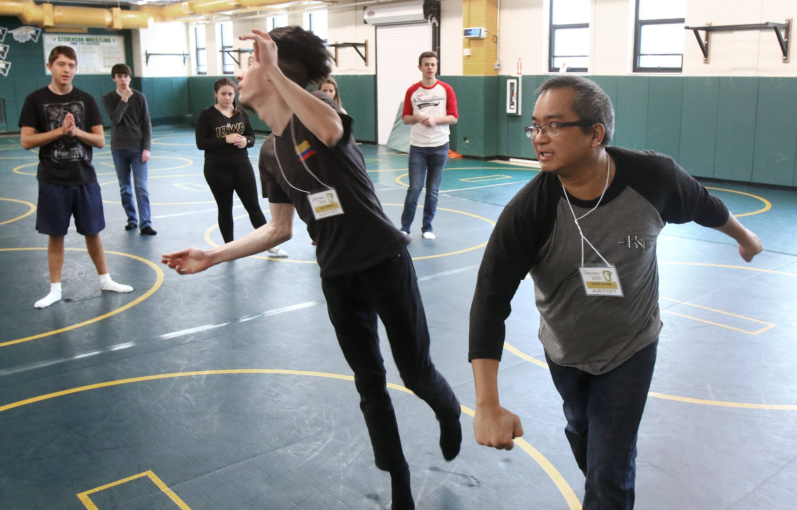 Instructor Victor Bayona pretends to hit his assistant Nicolas Cabrera in a combat fighting class Wednesday during the biennial Odyssey fine arts festival at Stevenson High School in Lincolnshire.