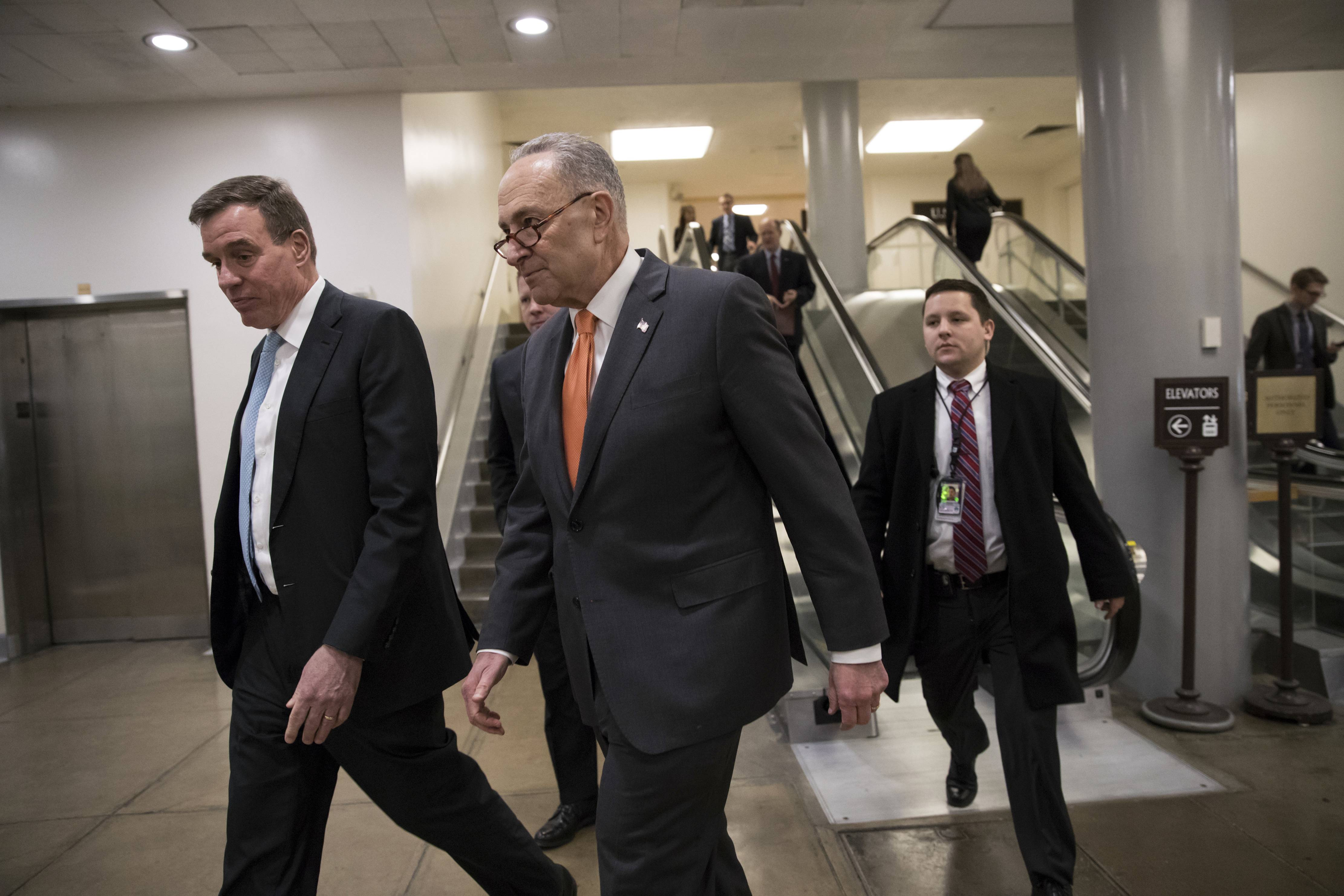 Senate Minority Leader Chuck Schumer, D-N.Y., center, and Sen. Mark Warner, D-Va., left, the vice chair of the Senate Select Committee on Intelligence, head to a closed security briefing at the Capitol in Washington, Tuesday, Feb. 6, 2018.
