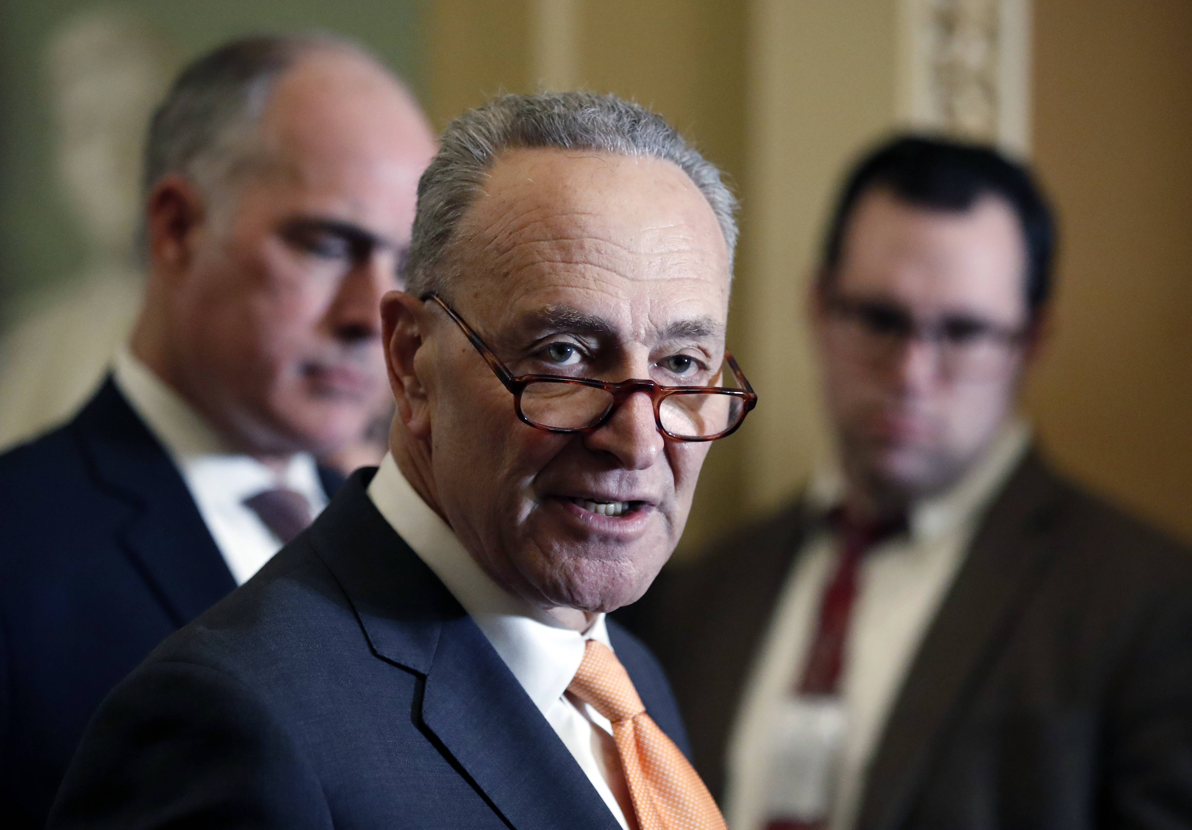 Senate Minority Leader Chuck Schumer of N.Y., center, accompanied by Sen. Bob Casey, D-Pa., at left, speaks on Capitol Hill, Tuesday, Feb. 6, 2018 in Washington.