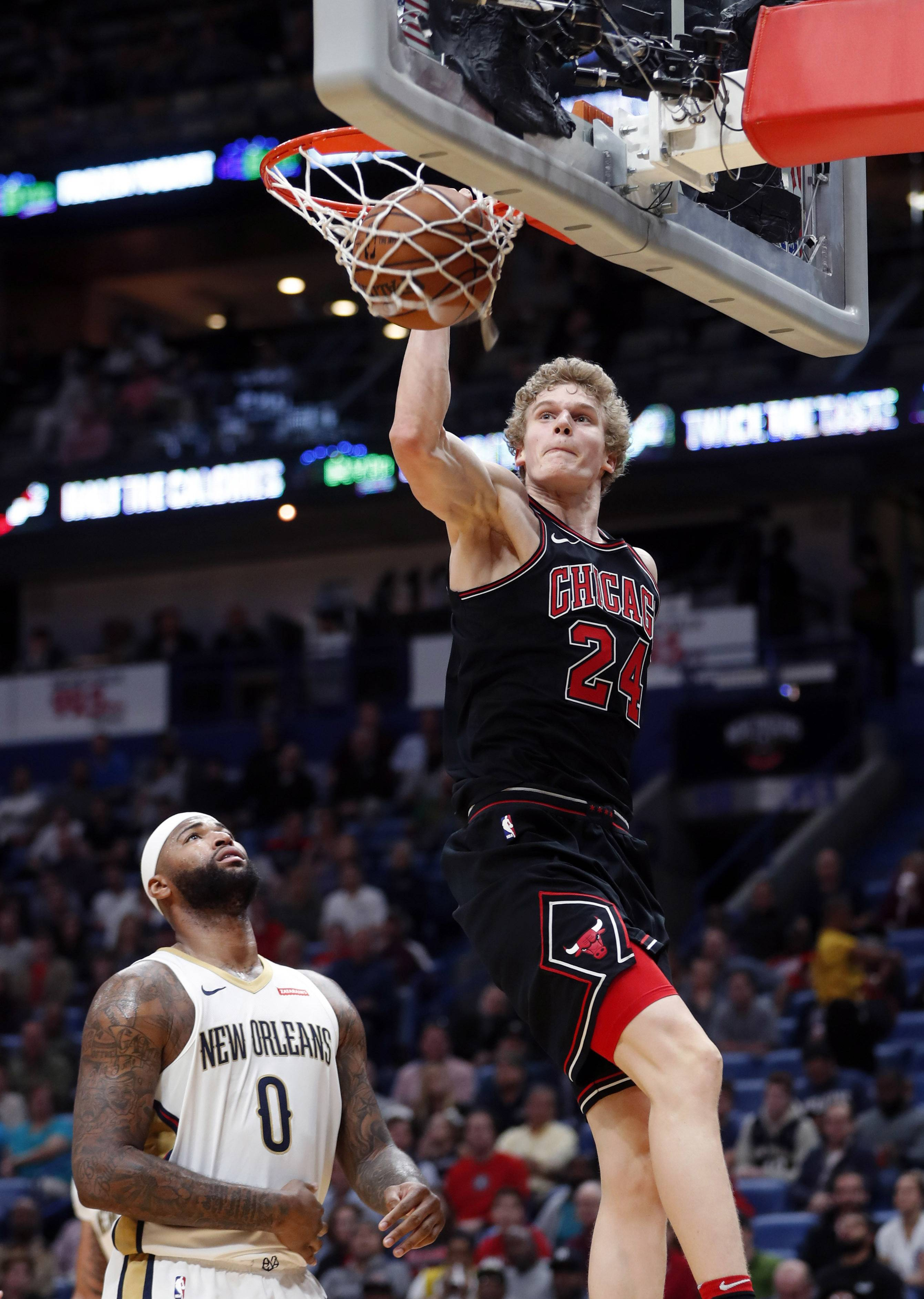 Chicago Bulls forward Lauri Markkanen (24) slam-dunks over New Orleans Pelicans center DeMarcus Cousins (0) in the first half of an NBA basketball game in New Orleans, Monday, Jan. 22, 2018.