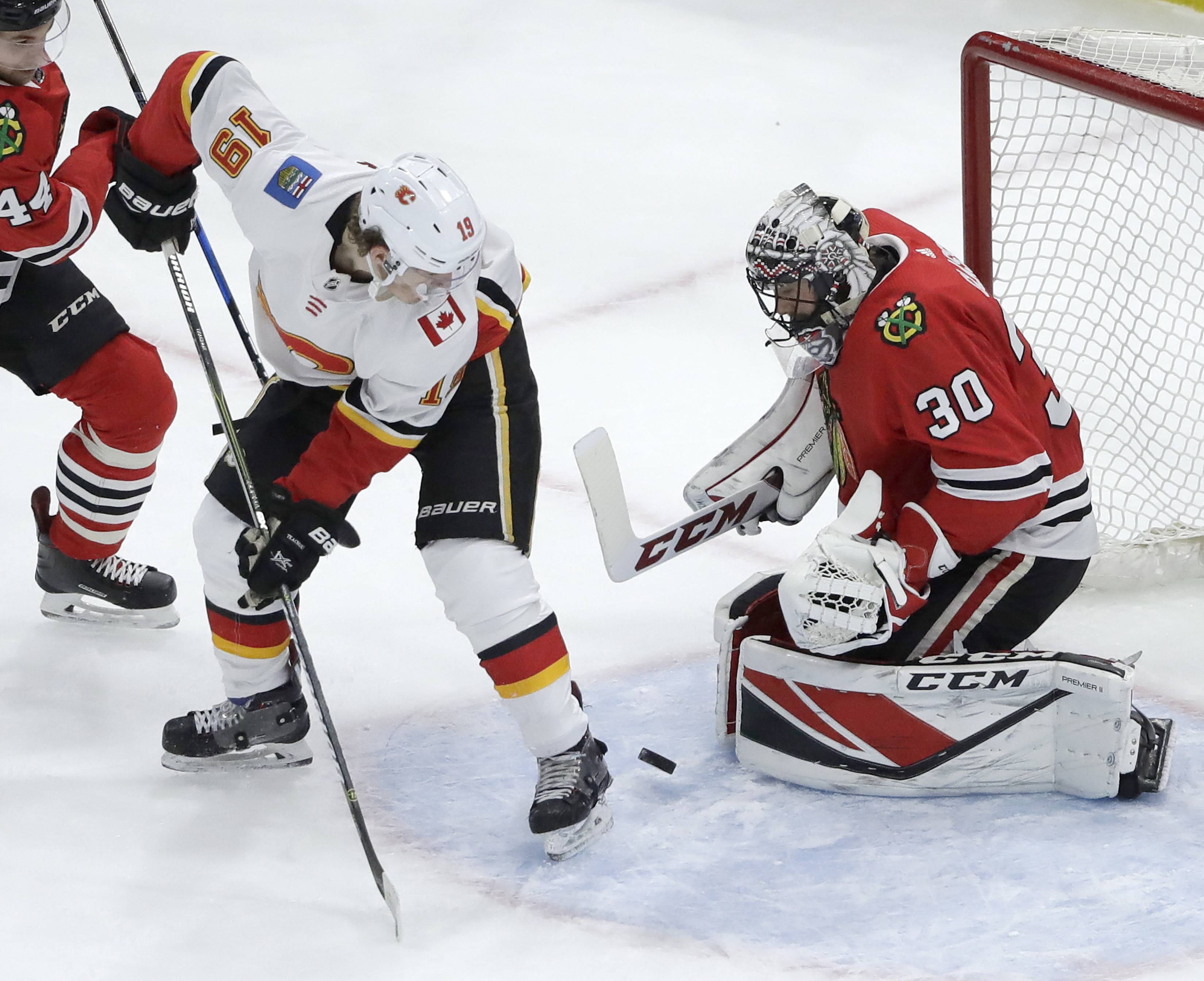 Chicago Blackhawks goaltender Jeff Glass (30) makes a save as Calgary Flames' Matthew Tkachuk (19) looks for the rebound during the first period of an NHL hockey game Tuesday, Feb. 6, 2018, in Chicago.