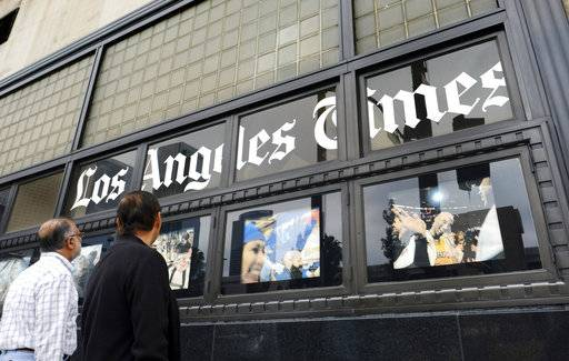FILE - In this May 16, 2016, file photo, pedestrians look at news photos posted outside the Los Angeles Times building in downtown Los Angeles. It was announced Wednesday, Feb. 7, 2018, that the Los Angeles Times is being sold to Dr. Patrick Soon-Shiong, a local billionaire, for $500 million, ending its strained tenure under the owner of the Chicago Tribune. Soon-Shiong is a major shareholder of Chicago's Tronc Inc., one of the richest men in Los Angeles and, according to Forbes, the nation's wealthiest doctor, with a net worth of $7.8 billion.