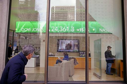 FILE- In this Feb. 6, 2018, file photo, a passer-by peers in the window while investors congregate inside at the Fidelity Investments office on Congress Street as the ticker displays stock market numbers in Boston. A plunge in stock prices always stings, but this recent one dug deeper because more of the country has become exposed to the ups and downs of the market, particularly older Americans.