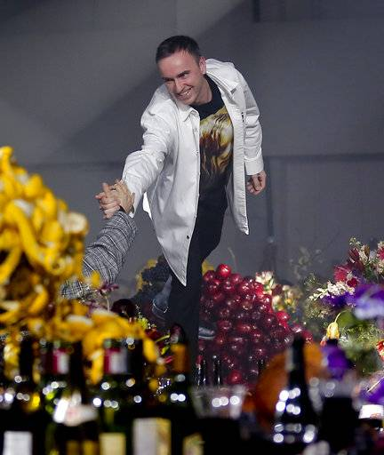 Fashion designer Raf Simons acknowledge cheers after unveiling his men's collection during Fashion Week, Wednesday, Feb. 7, 2018, in New York.
