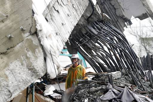 A rescuer checks damage during a search operation at a collapsed apartment building following a strong earthquake in Hualien County, eastern Taiwan, Thursday, Feb. 8, 2018. A magnitude 6.4 earthquake struck late Tuesday night caused several buildings to cave in and tilt dangerously.